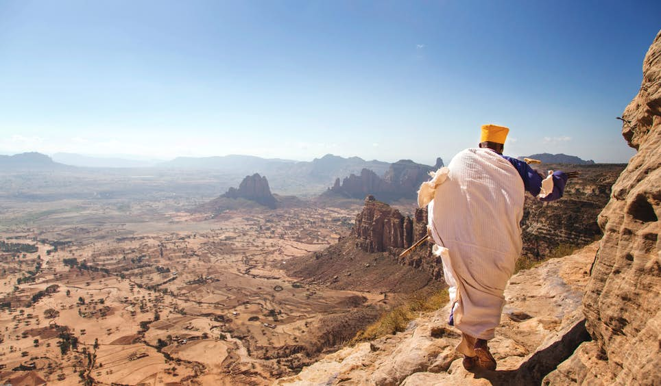 A priest on the precarious route up a mountain to one of Ethiopia's cave churches © Philip Lee Harvey / Lonely Planet